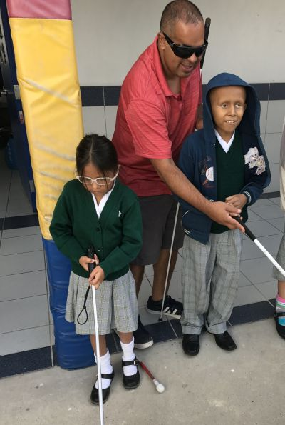 Richie, a METAS member teaching a student to use a cane