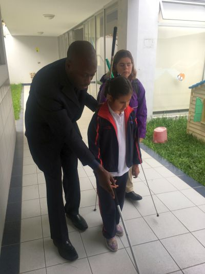 Garrick, a METAS member showing a student how to use a cane while a teacher looks on